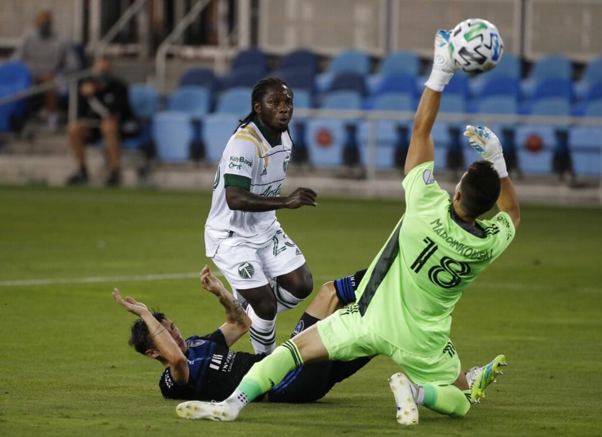 Portland Timbers forward Yimmi Chara (23), center, scores a goal against San Jose Earthquakes defender Paul Marie (33) and San Jose Earthquakes goalkeeper JT Marcinkowski (18), right, during the first half of an MLS soccer match Wednesday, Sept. 16, 2020, in San Jose, Calif.