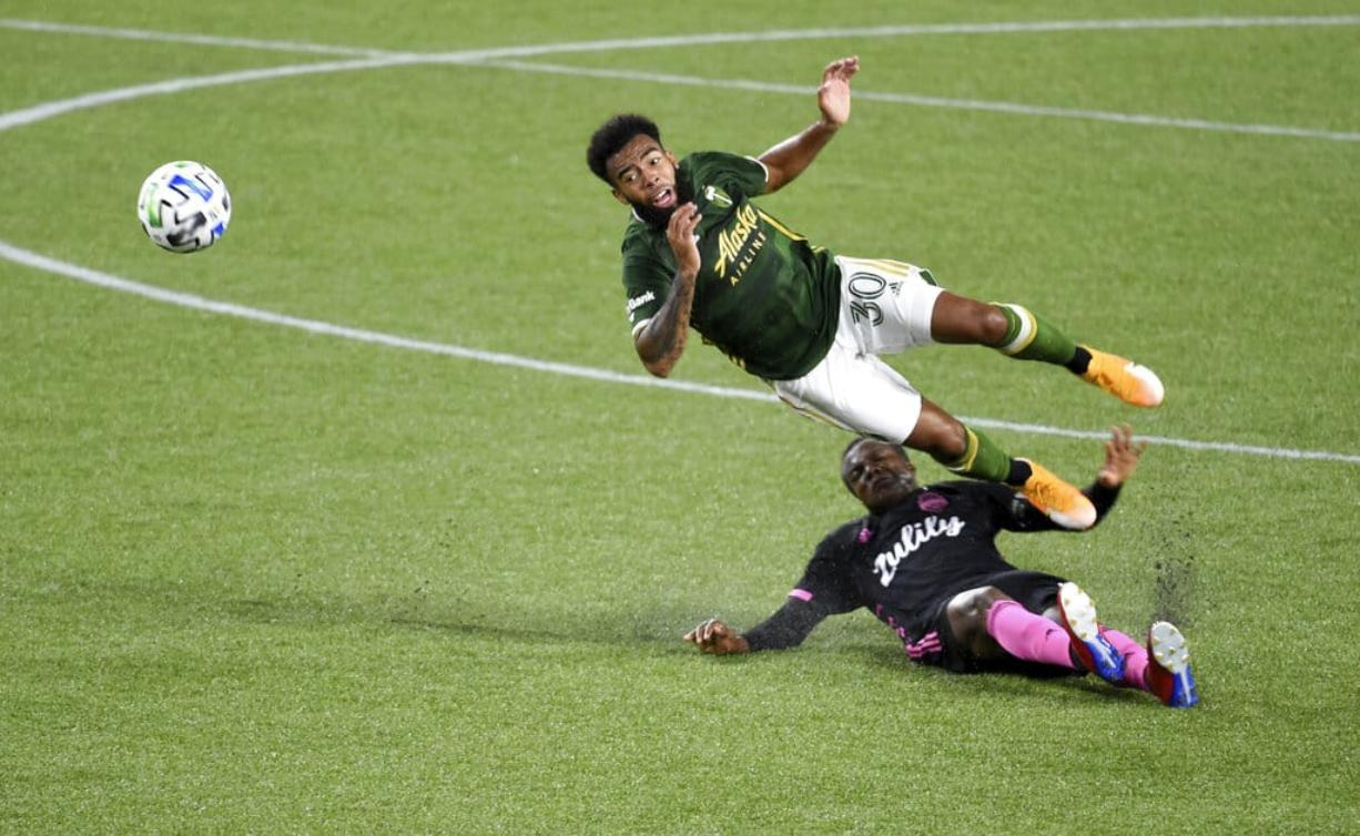 Portland Timbers midfielder Eryk Williamson, left, is upended by Seattle Sounders defender Nouhou Tolo during the first half of an MLS soccer match in Portland, Ore., Wednesday, Sept. 23, 2020.