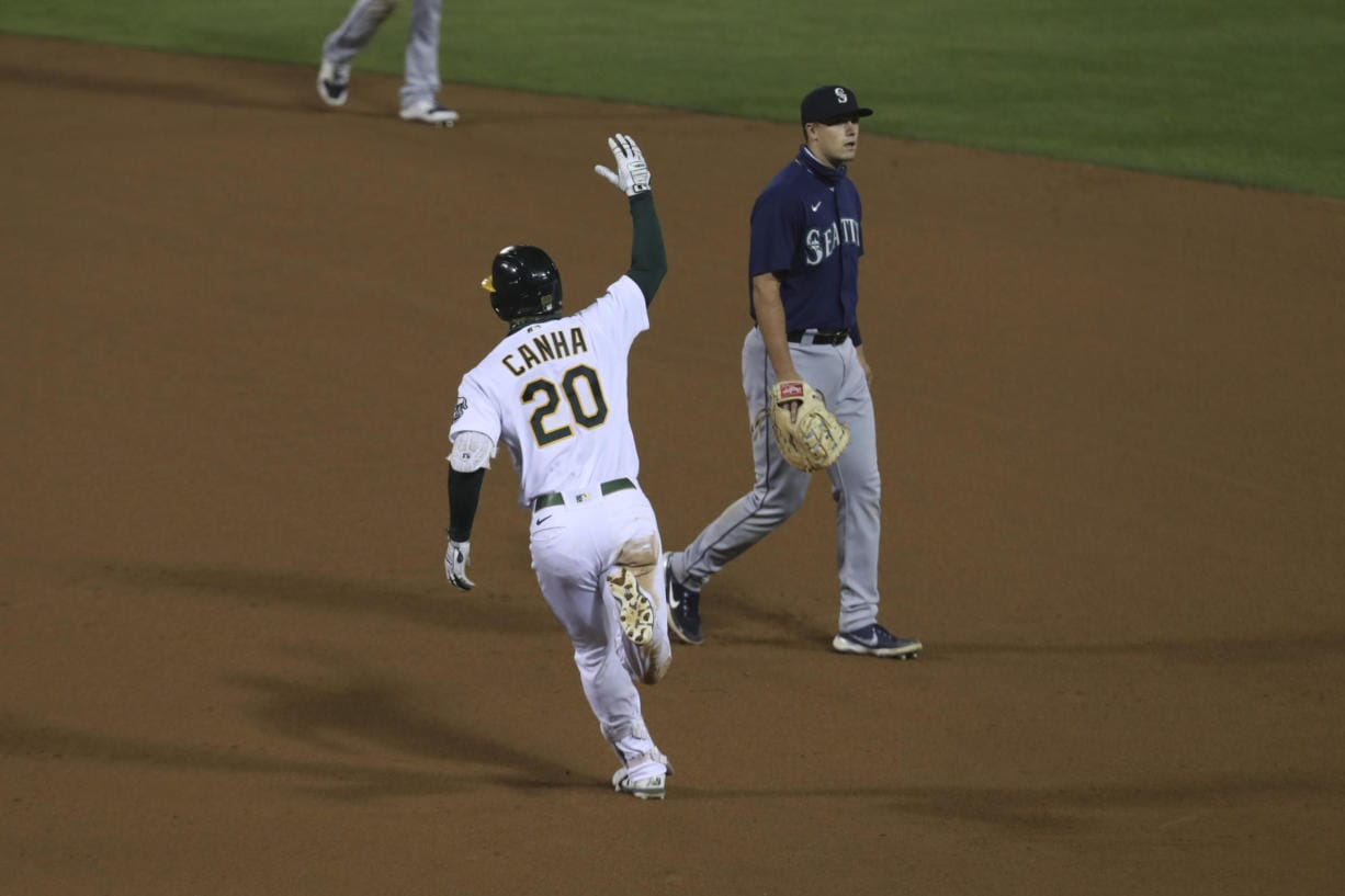 Oakland Athletics' Mark Canha (20) celebrates after hitting a game winning home run, while running past Seattle Mariners' Evan White during the 10th inning of a baseball game in Oakland, Calif., Friday, Sept. 25, 2020.