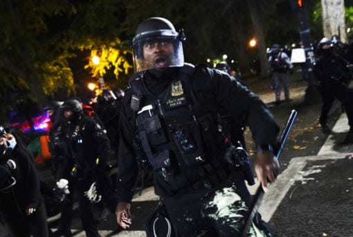 A Portland police officer pushes back protesters, Saturday, Sept. 26, 2020, in Portland. The protests, which began over the killing of George Floyd, often result frequent clashes between protesters and law enforcement.