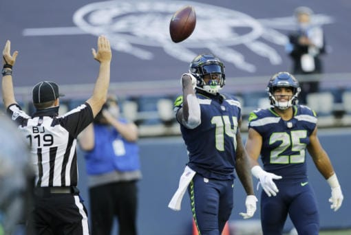 Seattle Seahawks wide receiver DK Metcalf (14) tosses the ball as he stands with running back Travis Homer (25) after Metcalf scored a touchdown against the Dallas Cowboys during the second half of an NFL football game, Sunday, Sept. 27, 2020, in Seattle.