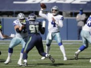 Dallas Cowboys quarterback Dak Prescott passes as Seattle Seahawks defensive end L.J. Collier blocks during the first half of an NFL football game, Sunday, Sept. 27, 2020, in Seattle.