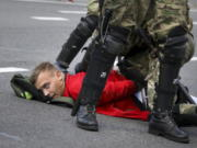 Riot police officers detain a protester during a Belarusian opposition supporters' rally protesting the official presidential election results in Minsk, Belarus, Sunday, Sept. 13, 2020. Protests calling for the Belarusian president's resignation have broken out daily since the Aug. 9 presidential election that officials say handed him a sixth term in office.