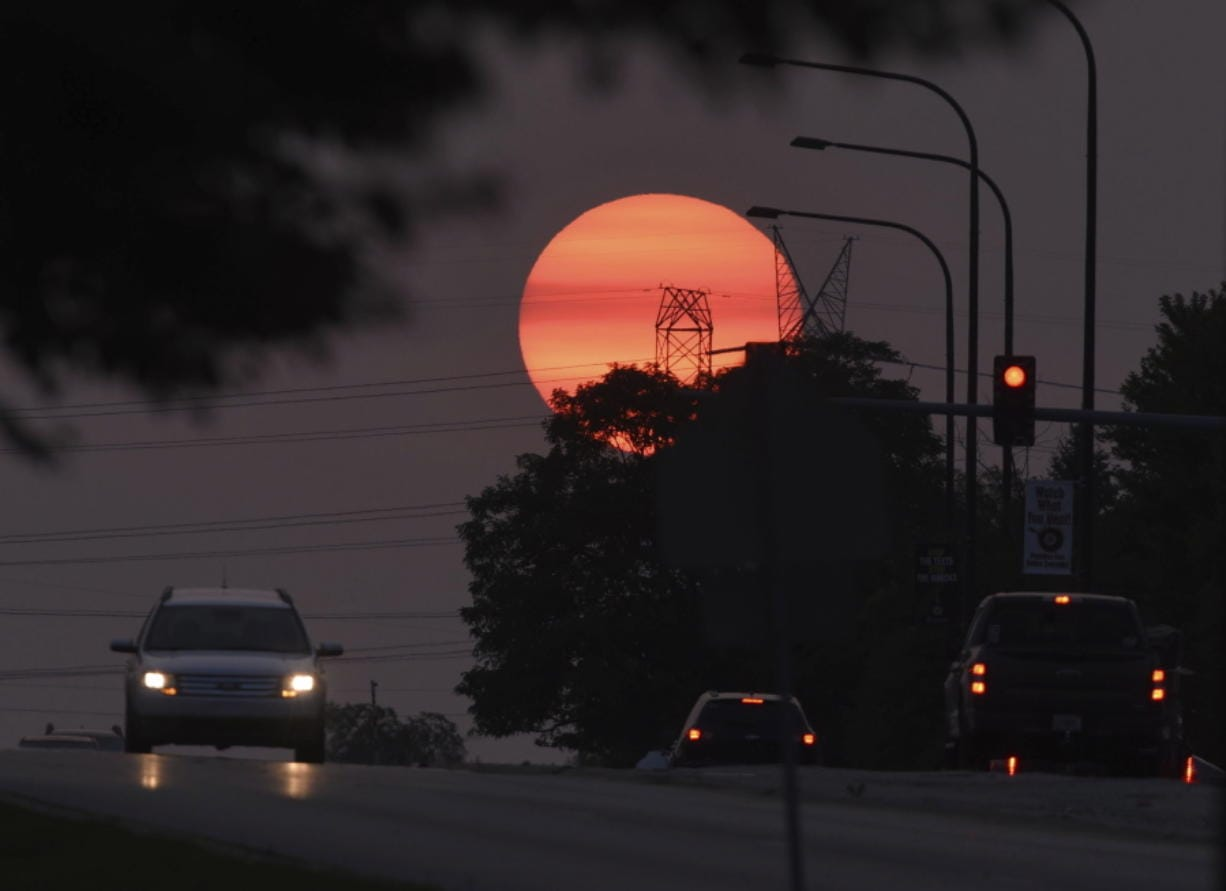 Traffic flows on Townline Road as a hazy sun sets in Vernon Hills, Ill,, Tuesday, Sept. 15, 2020.   The smoke from dozens of wildfires in the western United States has now blanket much of the county along with parts of Mexico and Canada, as residents thousands of miles away on the East Coast are being treated to unusually hazy skies and remarkable sunsets.