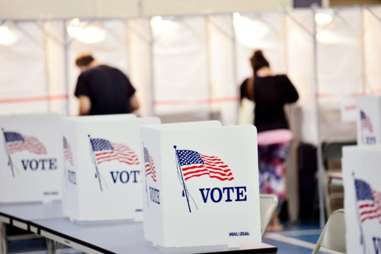 In this Sept. 8, 2020 photo, voting booths are kept socially distant at the Chesterfield, N.H. polling site.  A majority of President Donald Trump's supporters plan to cast their ballot on Election Day, while about half of Joe Biden's backers plan to vote by mail. That's according to a new poll from The Associated Press-NORC Center for Public Affairs Research that finds 54% of voters say they will vote before polls open on Nov. 3.