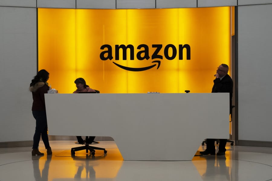 FILE - In this Feb. 14, 2019 file photo, people stand in the lobby for Amazon offices in New York. While other companies are shrinking, Amazon is growing. The company said Wednesday, Sept.