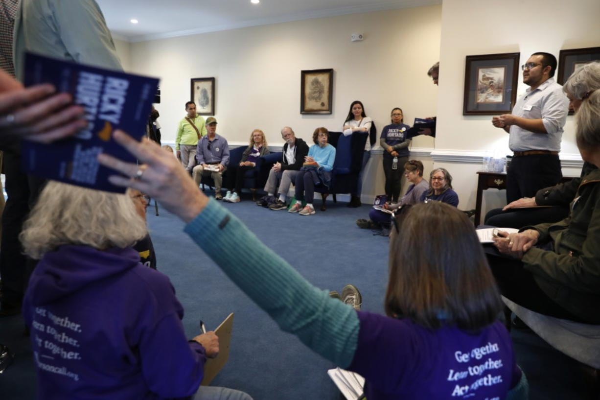 Ricky Hurtado, a Democratic candidate for the North Carolina state house, right, talks to volunteers before they head out to canvass voters, in Mebane, N.C., Sunday, March 8, 2020.