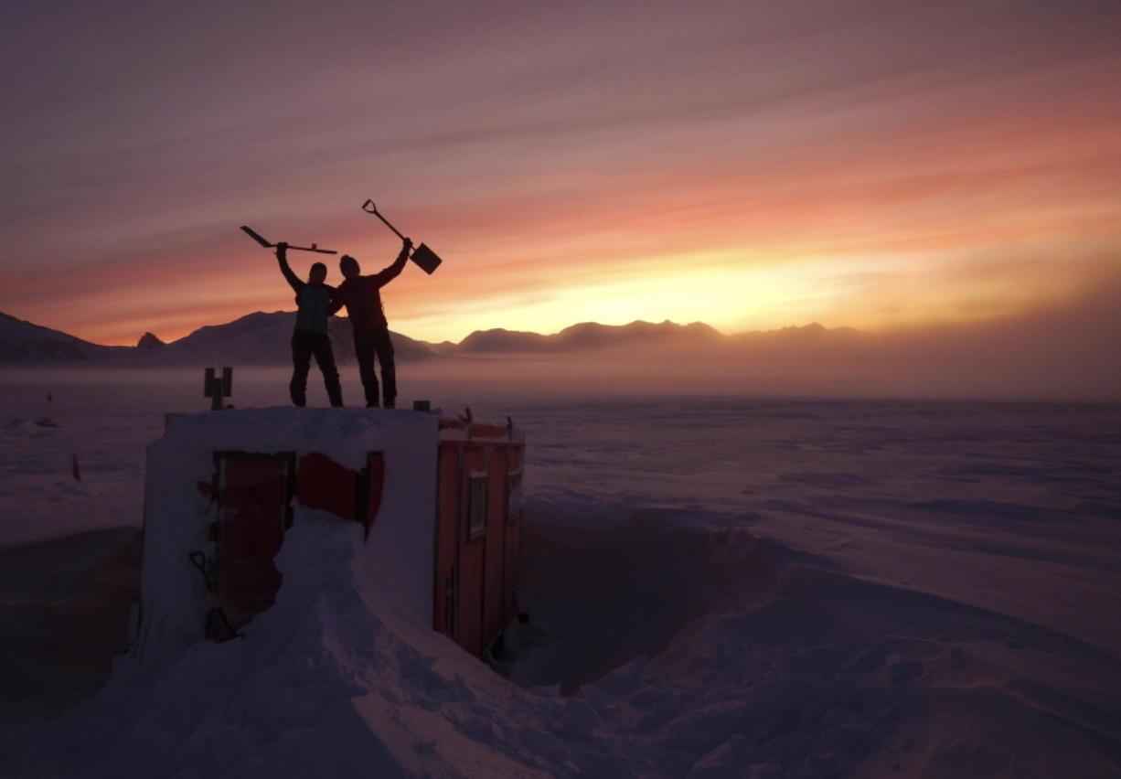In this handout photo provided by British Antarctic Survey, field guides Sarah Crowsley, left, and Sam Hunt, right, pose for a photo after digging out the caboose, a container used for accommodation that can be moved by a tractor, at Adelaide island, in Antarctica on Friday, June 19, 2020. Antarctica remains the only continent without COVID-19 and now in Sept. 2020, as nearly 1,000 scientists and others who wintered over on the ice are seeing the sun for the first time in months, a global effort wants to make sure incoming colleagues don't bring the virus with them.