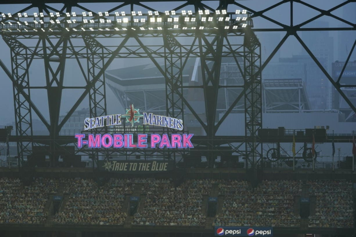 Smoke from wildfires fills the air at T-Mobile Park as photos of fans are displayed in the left field bleachers and CenturyLink Field is visible behind the ballpark sign during the second baseball game of a doubleheader between the Seattle Mariners and the Oakland Athletics, Monday, Sept. 14, 2020, in Seattle. (AP Photo/Ted S.
