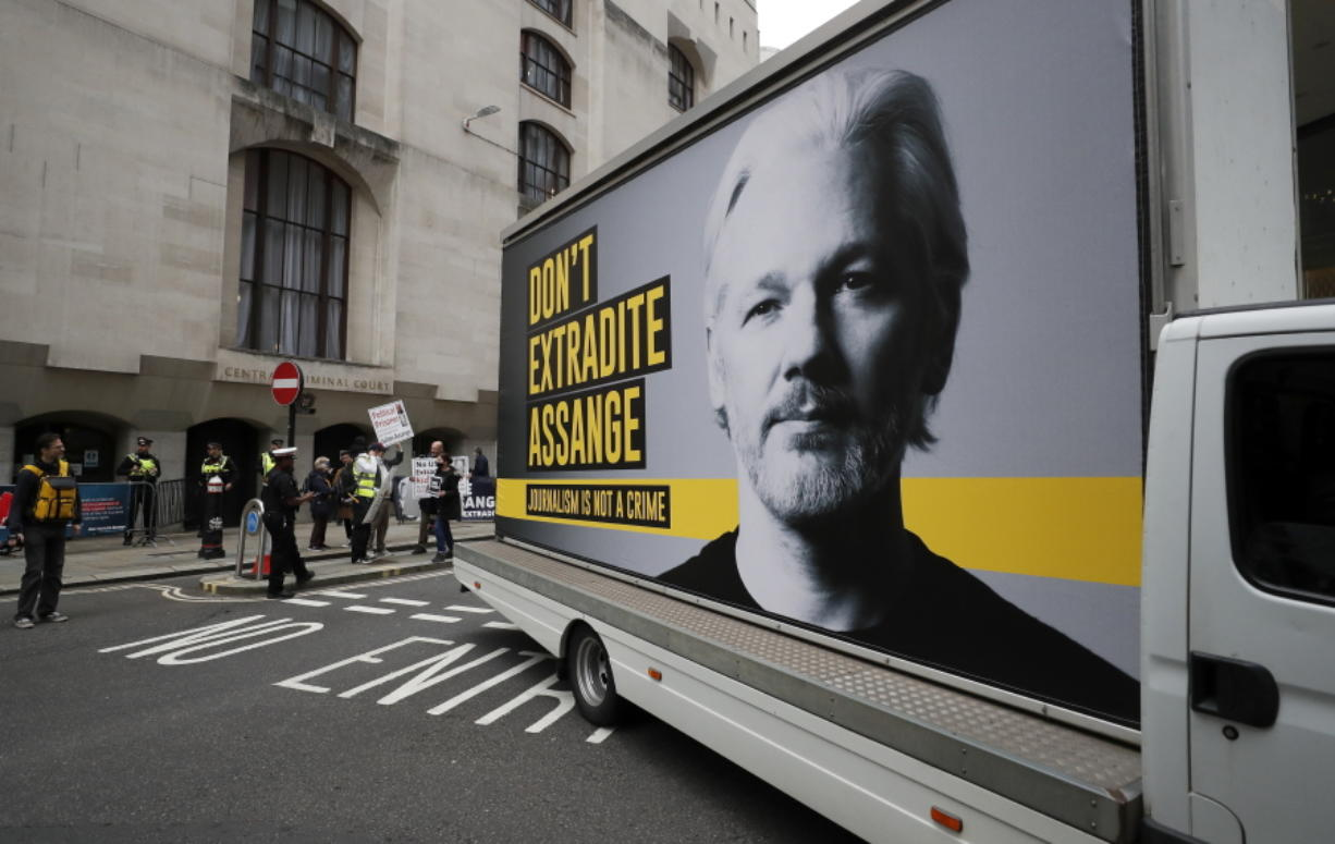 A van with a protest poster passes the Central Criminal Court Old Bailey in London, Monday, Sept. 7, 2020. Lawyers for WikiLeaks founder Julian Assange and the U.S. government were squaring off in a London court on Monday at a high-stakes extradition case delayed by the coronavirus pandemic. American prosecutors have indicted the 49-year-old Australian on 18 espionage and computer misuse charges over Wikileaks' publication of secret U.S. military documents a decade ago. The charges carry a maximum sentence of 175 years in prison.