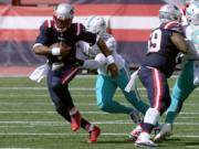 New England Patriots quarterback Cam Newton, front, runs from Miami Dolphins linebacker Kyle Van Noy (53)in the first half of an NFL football game, Sunday, Sept. 13, 2020, in Foxborough, Mass.