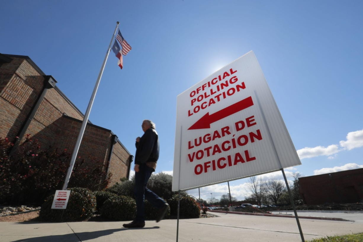 FILE - In this Feb. 26, 2020 file photo, using both the English and Spanish language, a sign points potential voters to an official polling location during early voting in Dallas.  Getting enough people to staff polling places amid the coronavirus pandemic is a challenge in many states. The virus' disproportionate impact on Latinos has made the task of recruiting Spanish-speakers even more difficult.