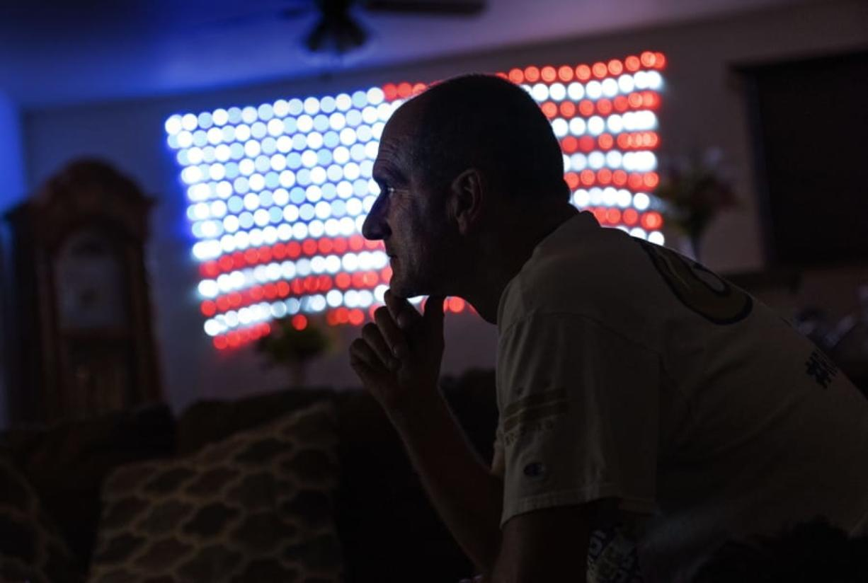 Scott Rice sits in his living room watching a Fox News Channel interview with President Donald Trump in Appleton, Wis., Aug. 20, 2020. Nothing can shake Rice's faith that Trump will save the U.S. economy, not seeing businesses close or friends furloughed, not even his own hellish bout with the coronavirus. But in Appleton, a city of 75,000 people along the Fox River, the health of economy isn't judged on jobs numbers, personal bank accounts or union contracts. Instead, it's viewed through partisan lenses, filtered through the facts voters want to see and hear, and those they don't.