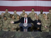 "FILE - In this Nov. 28, 2019 file photo, President Donald Trump, center, with Afghan President Ashraf Ghani and Joint Chiefs Chairman Gen. Mark Milley, behind him at right, addresses members of the military during a surprise Thanksgiving Day visit at Bagram Air Field, Afghanistan. During his election campaign four years ago, Trump vowed to bring all troops home from ""endless wars."" In recent months he's only increased the pressure, working to fulfill his campaign promise and get forces home before Election Day."