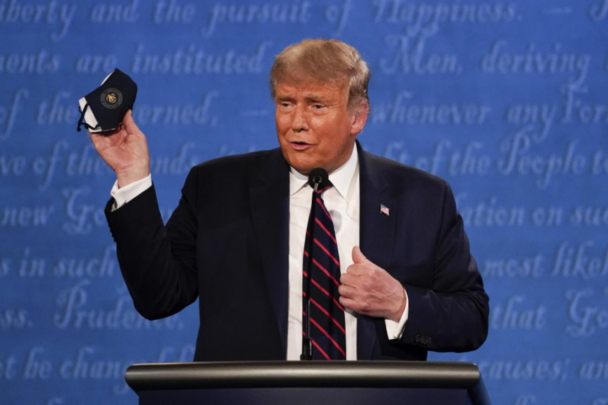 President Donald Trump holds up his face mask during the first presidential debate Tuesday, Sept. 29, 2020, at Case Western University and Cleveland Clinic, in Cleveland, Ohio.