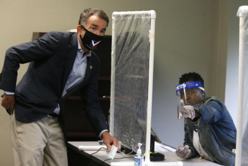 Virginia Gov. Ralph Northam, left, is shown by a poll worker which way to go as he votes early at the Richmond general registrar's office in Richmond, Va., Friday, Sept. 18, 2020, on the first day of Virginia's 45-day early voting period.