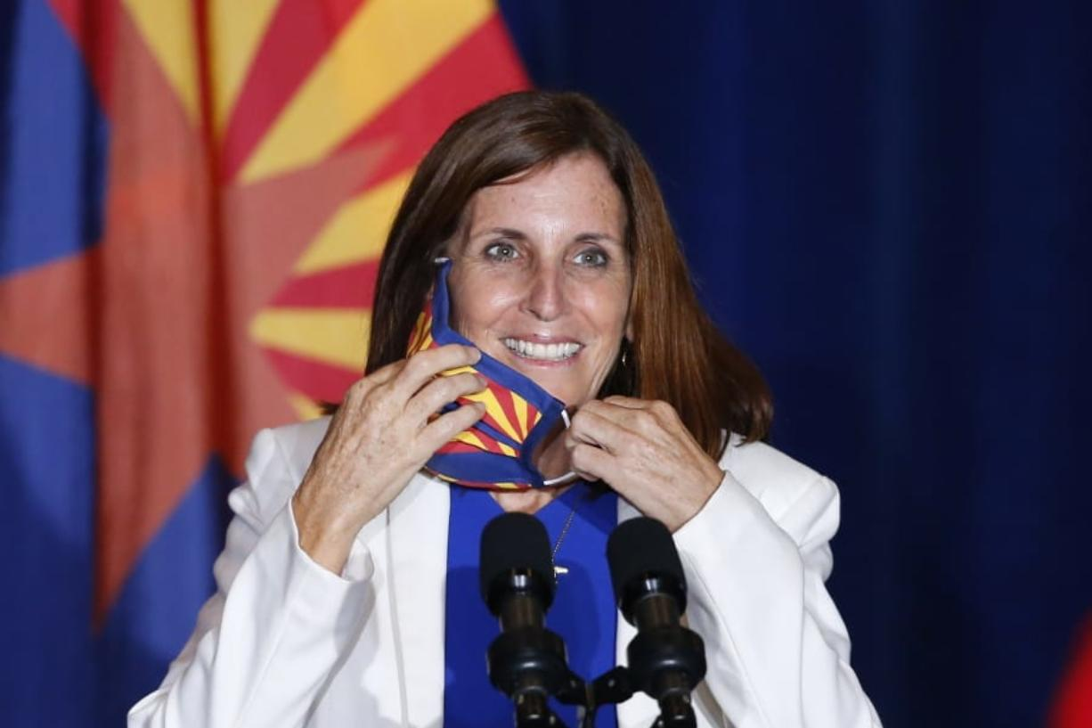 """FILE - In this Tuesday, Aug. 11, 2020 file photo, Sen. Martha McSally, R-Ariz., smiles as she removes her face covering to speak prior to Vice President Mike Pence arriving to speak at the """"Latter-Day Saints for Trump"""" coalition launch event in Mesa, Ariz. McSally has suggested that supporters could """"fast a meal"""" to donate to the Arizona Republican's campaign as she fights to fend off a tough challenge from Democrat Mark Kelly in the November 2020 election. (AP Photo/Ross D."""