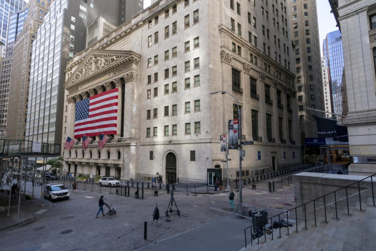 FILE - In this Monday, Sept. 21, 2020 file photo, a giant American Flag hangs on the New York Stock Exchange. Wall Street is rallying Wednesday, Sept. 30 on rising hopes that Washington may pierce through its paralyzing partisanship to offer more aid for the economy.