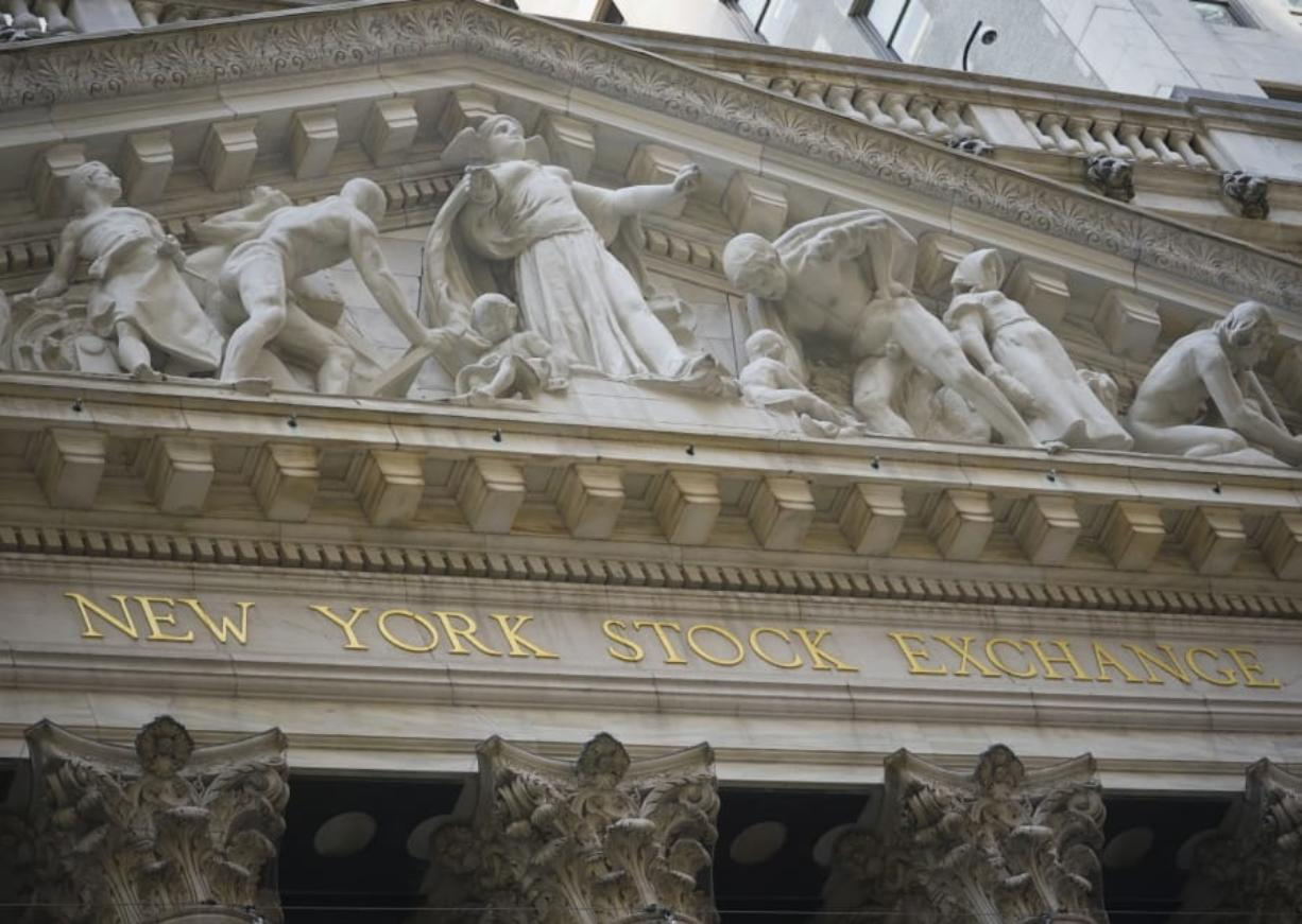 FILE - Marble sculptures occupy the pediment above the New York Stock Exchange signage, Tuesday Aug. 25, 2020, in New York.  Stocks are drifting in mixed trading on Wall Street Friday, Sept.