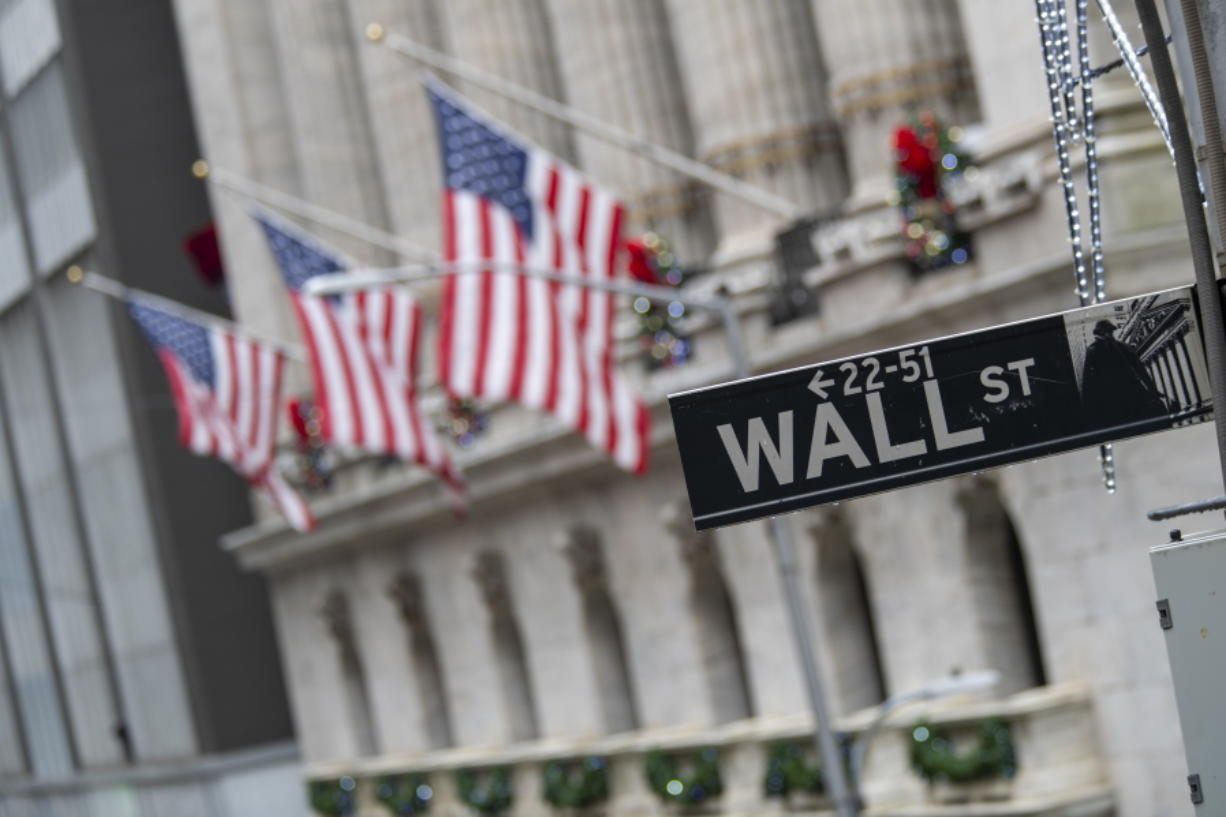 FILE - In this Jan. 3, 2020 file photo, the Wall St. street sign is framed by American flags flying outside the New York Stock Exchange in New York.  Stocks are falling early on Wall Street Thursday, Sept. 17,  as the late selling from the previous day carries over.