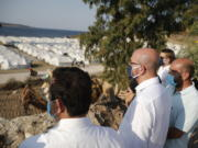 European Council President Charles Michel, center, accompanied by Greek officials, looks at the new temporary refugee camp in Kara Tepe during his visit on the northeastern island of Lesbos, Greece, Tuesday, Sept. 15, 2020.