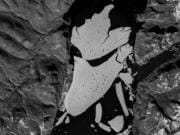 In this image proved by the European Space Agency, ESA, showing the glacier section that broke off the fjord called Nioghalvfjerdsfjorden, bottom, which is roughly 80 kilometers (50 miles) long and 20 kilometers (12 miles) wide, the National Geological Survey of Denmark and Greenland said Monday Sept. 14, 2020. The glacier is at the end of the Northeast Greenland Ice Stream, where it flows off land and into the ocean. Scientists with National Geological Survey see it as evidence of rapid climate change leading to the disintegration of the Arctic's largest remaining ice shelf.
