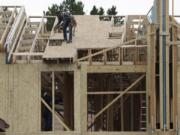 Workers toil on a multifamily dwelling Tuesday, Aug. 4, 2020, in Winter Park, Colo.   The Commerce Department reported Tuesday, Aug. 18, construction of new U.S. homes surged 22.6 percent last month as homebuilders continued to bounce back from the coronavirus pandemic.