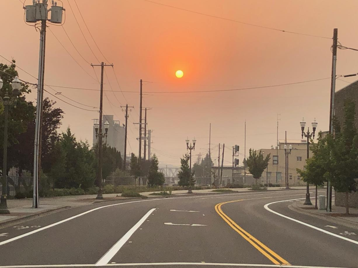 The sun sets through wildfire smoke in downtown Vancouver on Monday evening as strong east winds buffeted Clark County.