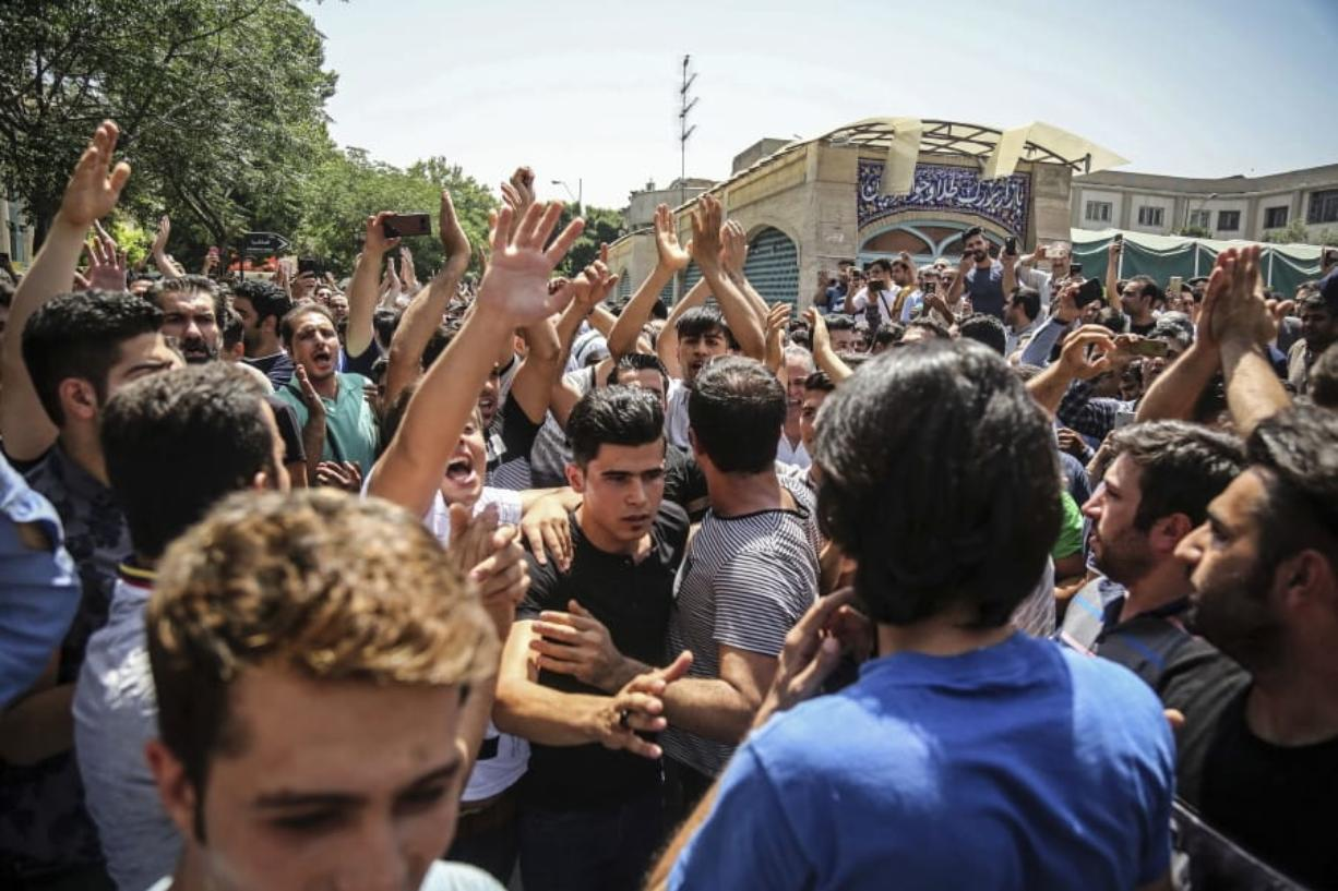 FILE - In this June 25, 2018 file photo, a group of protesters chant slogans at the main gate of the Old Grand Bazaar, in Tehran, Iran. On Saturday, Sept. 5, 2020, Iran broadcast the televised confession of a wrestler facing the death penalty after a tweet from President Donald Trump criticizing the case, a segment that resembled hundreds of other suspected coerced confessions aired over the last decade in the Islamic Republic. The case of 27-year-old Navid Afkari has drawn the attention of a social media campaign that portrays him and his brothers as victims targeted over participating in protests against Iran's Shiite theocracy in 2018.