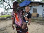 Fakisha Fenderson and her son Tyler stand in the front yard of her parent's home in Laurel, Miss., Monday, Aug. 31, 2020. Fenderson's weekly unemployment allotment is under $100, effectively eliminating her chance at receiving the $300 weekly supplement proposed by President Trump's executive order. (AP Photo/Rogelio V. Solis) (rogelio v.