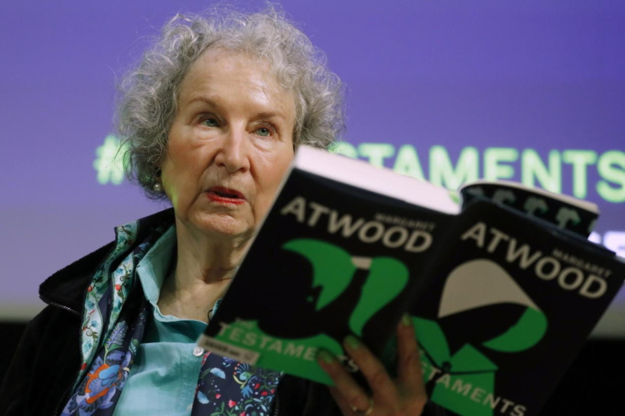 "FILE - In this Sept. 10, 2019, file photo, Canadian author Margaret Atwood holds a copy of her book ""The Testaments,"" during a news conference in London. Atwood, whose sweeping body of work includes ""The Handmaid's Tale,"" depicting a nightmarish future for the United States, is this year's winner of a lifetime achievement award celebrating literature's power to foster peace, social justice and global understanding, officials of the Dayton Literary Peace Prize officials announced Monday, Sept. 14, 2020."