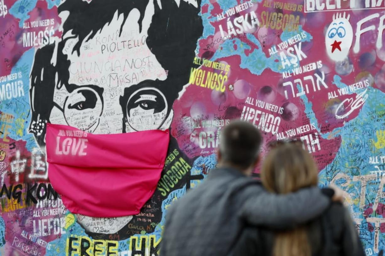 """A couple look at the """"Lennon Wall"""" with a face mask attached to the image of John Lennon, in Prague, Czech Republic, on April 6. Like so many other events in the year of coronavirus, an annual tribute to John Lennon held in his adopted city of New York will go online."""