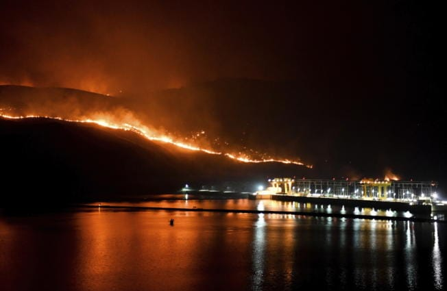Flames from the Cold Springs Canyon Pearl Hill wildfire encroach on Wells Dam, Monday, Sept. 7, 2020, near Azwell, Wash.
