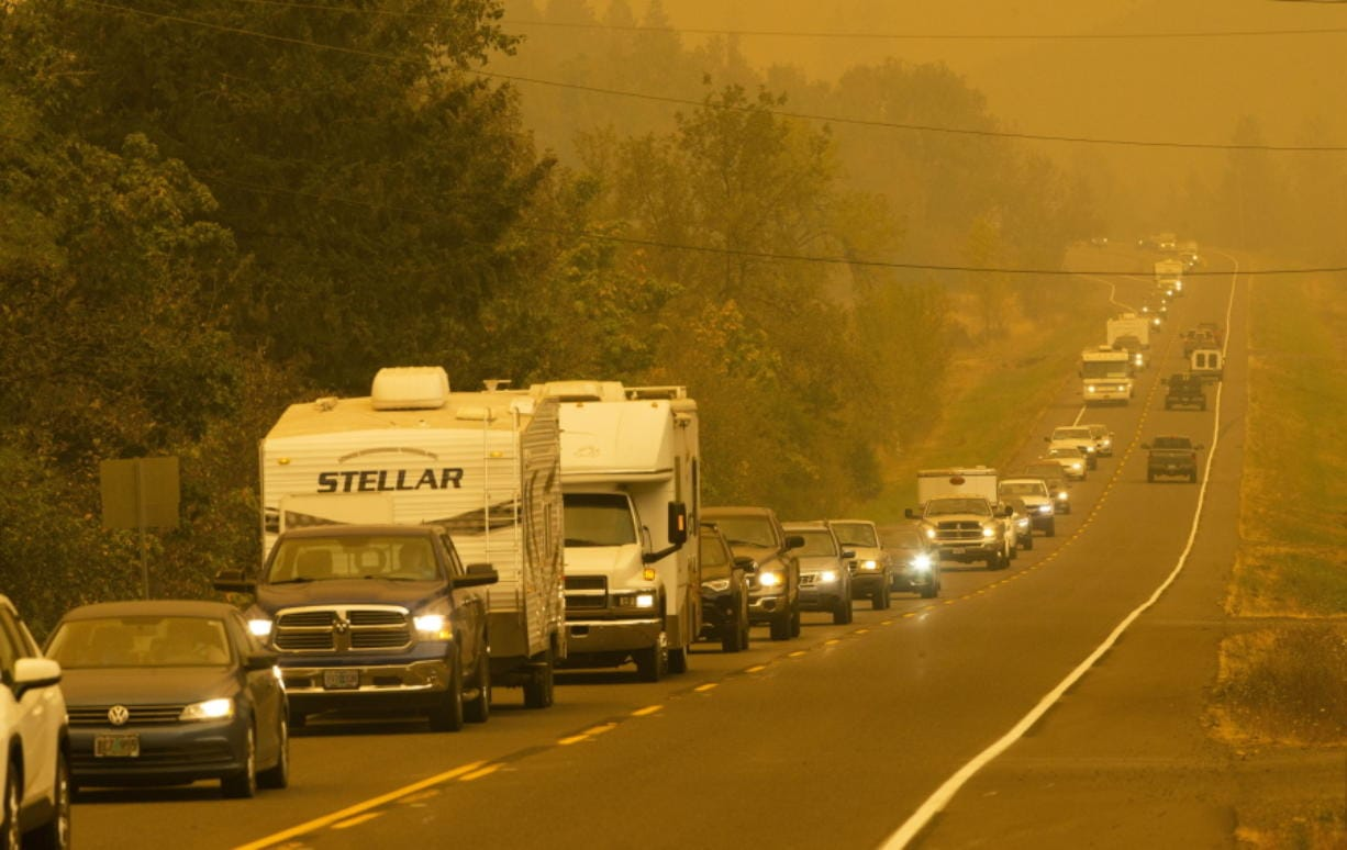 A steady stream of vehicles heads west on a road east of Springfield, Ore., as residents evacuate the area ahead of a fast-moving wildfire Tuesday Sept. 8, 2020.