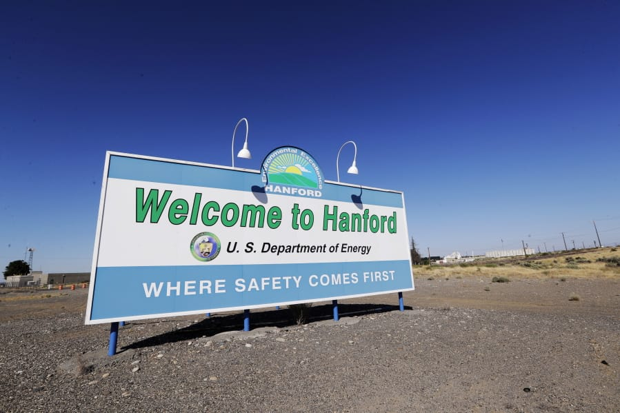 FILE - In this Aug. 13, 2019, file photo, a sign at the Hanford Nuclear Reservation is posted near Richland, Wash. Two companies that do work at the former nuclear weapons production plant will pay fines of nearly $58 million for improperly billing the federal government for thousands of hours of work that were not performed.