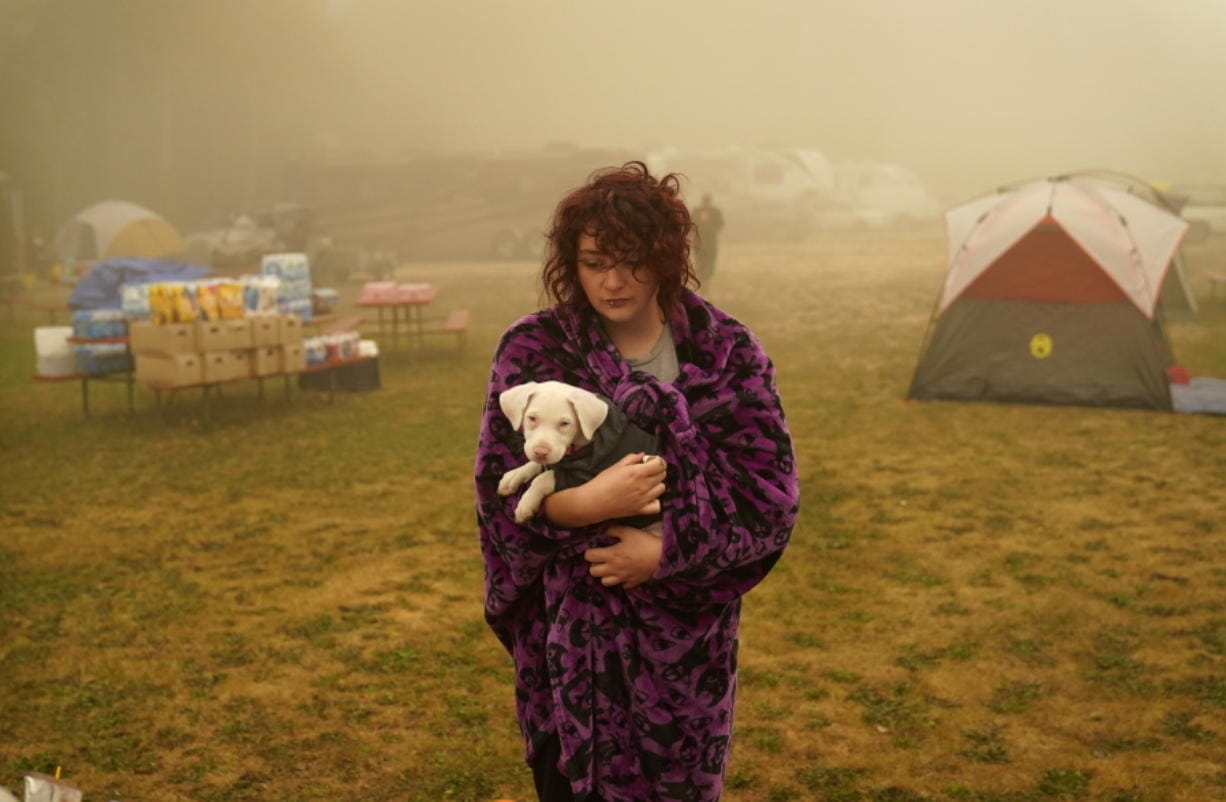 """Shayanne Summers holds her dog Toph while wrapped in a blanket after several days of staying in a tent at an evacuation center at the Milwaukie-Portland Elks Lodge, Sunday, Sept. 13, 2020, in Oak Grove, Ore. """"It's nice enough here you could almost think of this as camping and forget everything else, almost,"""" said Summers about staying at the center after evacuating from near Molalla, Oregon which was threatened by the Riverside Fire."""