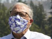 Washington Gov. Jay Inslee wears a mask as he talks to reporters, Wednesday, Sept. 9, 2020, following a tour to survey wildfire damage in Bonney Lake, Wash., south of Seattle. (AP Photo/Ted S.