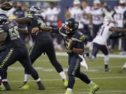 Seattle Seahawks quarterback Russell Wilson passes against the New England Patriots during the second half of an NFL football game, Sunday, Sept. 20, 2020, in Seattle.