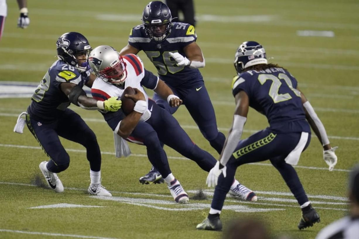 New England Patriots quarterback Cam Newton is tackled by Seattle Seahawks safety Ugo Amadi, left, as linebacker Jordyn Brooks, second from right, and cornerback Tre Flowers, right, provide added pressure.