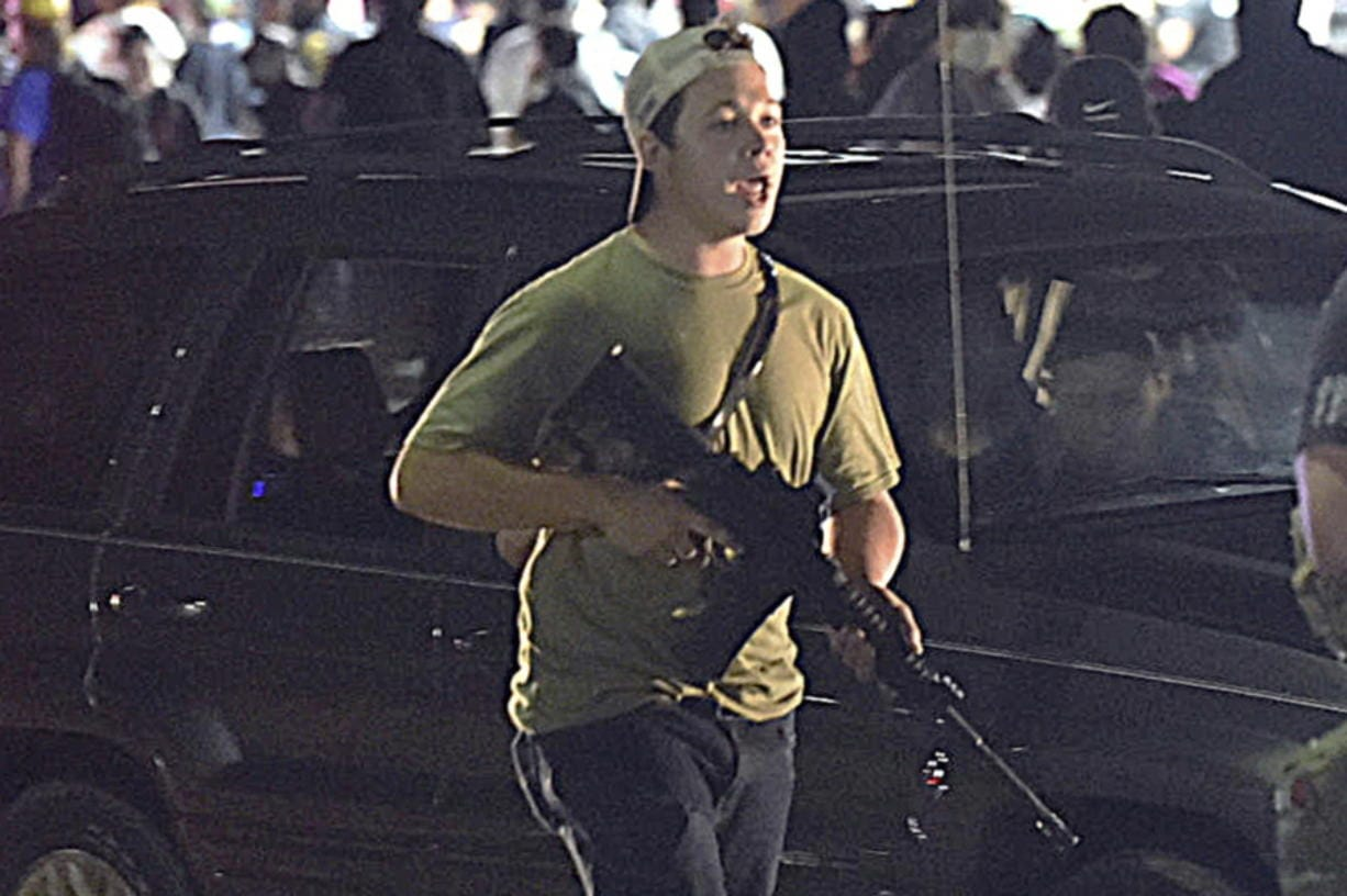 FILE - In this Tuesday, Aug. 25, 2020 file photo, Kyle Rittenhouse carries a weapon as he walks along Sheridan Road in Kenosha, Wis., during a night of unrest following the weekend police shooting of Jacob Blake. The way his lawyers tell it, the teenager wasn't a scared, gun enthusiast in over his head when he fatally shot two protesters. He was a courageous defender of liberty, a patriot exercising his right to bear arms amid chaos in the streets. But some legal experts say Rittenhouse's lawyers are taking big risks by turning a fairly straightforward self-defense case into a sweeping political argument that mirrors the law-and-order re-election campaign of President Donald Trump.