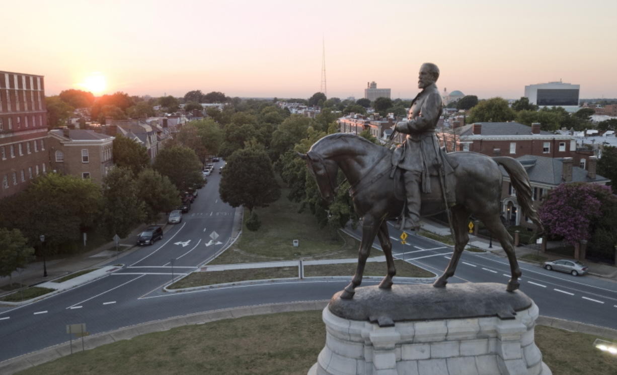 FILE - In this July 31, 2017, file photo, the sun sets behind the statue of Confederate Gen. Robert E. Lee on Monument Avenue in Richmond, Va. In a state where Confederate monuments have stood for more than a century and have recently become a flashpoint in the national debate over racial injustice, Virginians remain about evenly divided on whether the statues should stay or go, according to a new poll. The poll conducted this month by Hampton University and The Associated Press-NORC Center for Public Affairs Research found that 46% support removal of Confederate statues and 42% oppose removal.