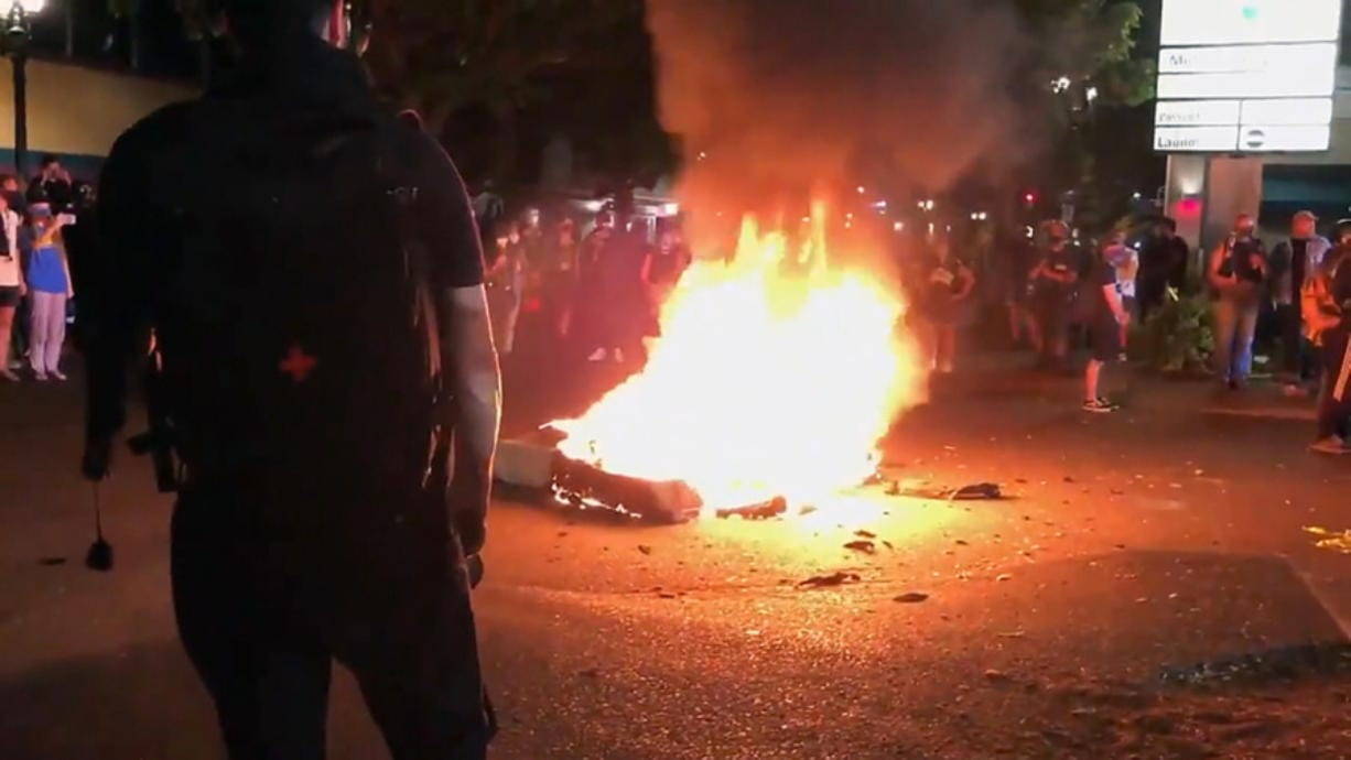 In this image taken from video a mattress burns in the street near the Portland Police Bureau's North Precinct Sunday night, Sept. 6, 2020, in Portland, Ore. Protesters have gathered for more than 100 days following the death of George Floyd in Minneapolis.