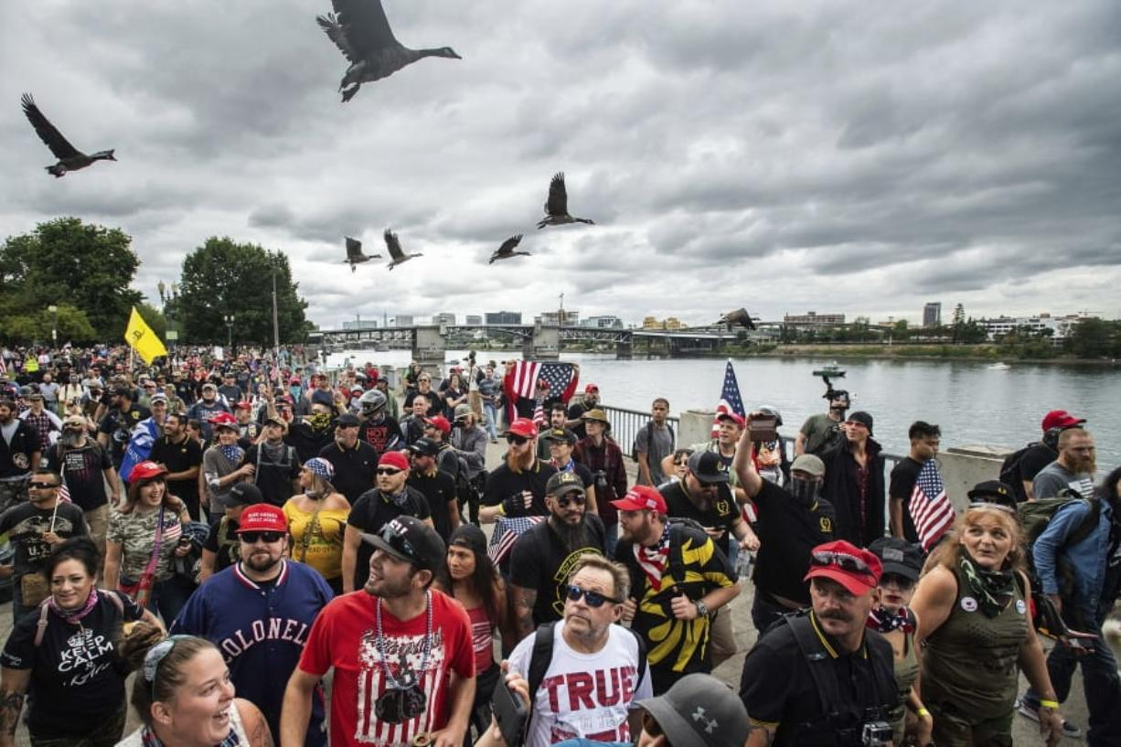 FILE - In this Aug. 17, 2019, file photo, members of the Proud Boys and other right-wing demonstrators march along the Willamette River during a rally in Portland, Ore. Portland has denied a permit for a Saturday rally planned by the right-wing group Proud Boys. The Portland Parks & Recreation Bureau said Wednesday, Sept. 23, 2020, that the group's estimated crowd size of 10,000 people was too big under coronavirus safety measures.