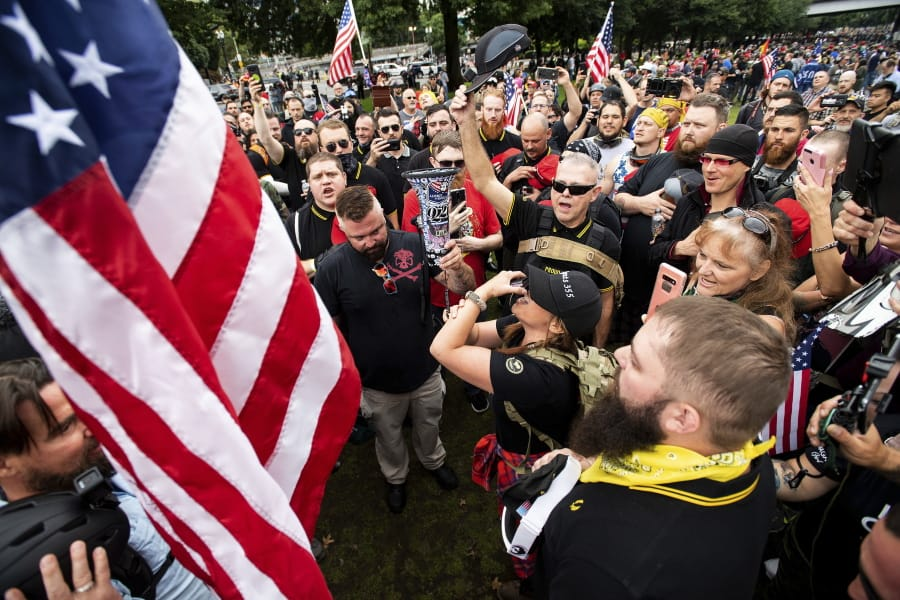 FILE - In this Aug. 17, 2019, file photo, members of the Proud Boys and other right-wing demonstrators plant a flag in Tom McCall Waterfront Park during a rally in Portland, Ore. At least several thousand people are expected in Portland on Saturday, Sept. 26, 2020, for a rally in support of President Donald Trump and his re-election campaign as tensions boil over nationwide following the decision not to charge officers in Louisville, Kentucky for killing Breonna Taylor.