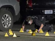 A Washington State Patrol Crime Lab worker looks at evidence markers in the early morning hours of Sept. 4 in Lacey, at the scene where Michael Reinoehl was killed as investigators moved in to arrest him. (Ted S.