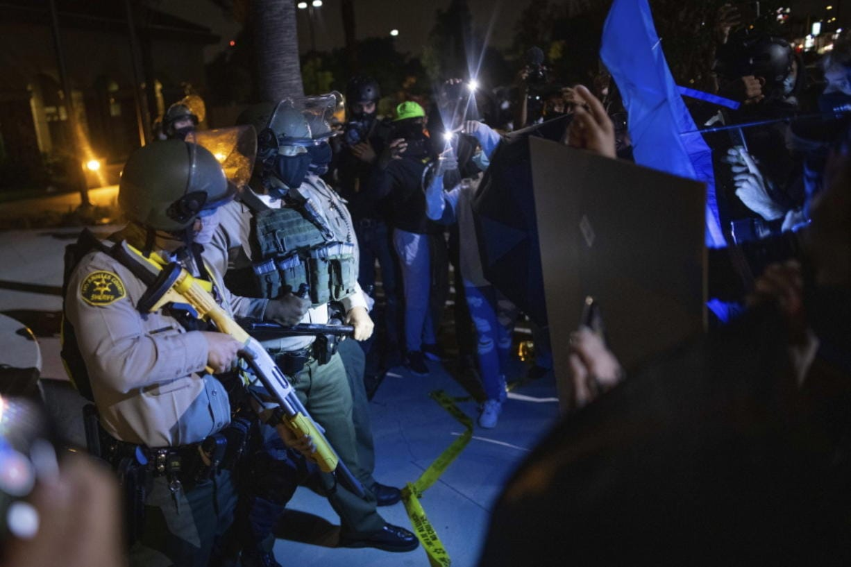 Protesters clash with deputies of the Los Angeles Sheriff's Department during protests following the death of Dijon Kizzee on Monday, Aug. 31, 2020, in Los Angeles, Calif.
