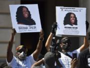 FILE - Signs are held up showing Breonna Taylor during a rally in her honor on the steps of the Kentucky State Capitol in Frankfort, Ky., Thursday, June 25, 2020. The city of Louisville will pay several million dollars to the mother of Breonna Taylor and install police reforms as part of a settlement of a lawsuit from Taylor's family, The Associated Press has learned. (AP Photo/Timothy D.