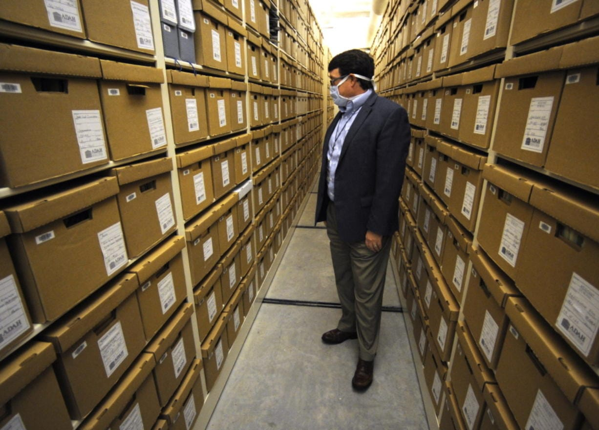 "Steve Murray, director of the Alabama Department of Archives and History, looks through boxes containing archival materials in Montgomery, Ala., on Thursday, Aug. 13, 2020. Murray and other current leaders of the agency are confronting the early legacy of the department, which once embraced the ""lost cause"" version of Civil War history that diminished the role of slavery and portrayed the Southern cause as noble."
