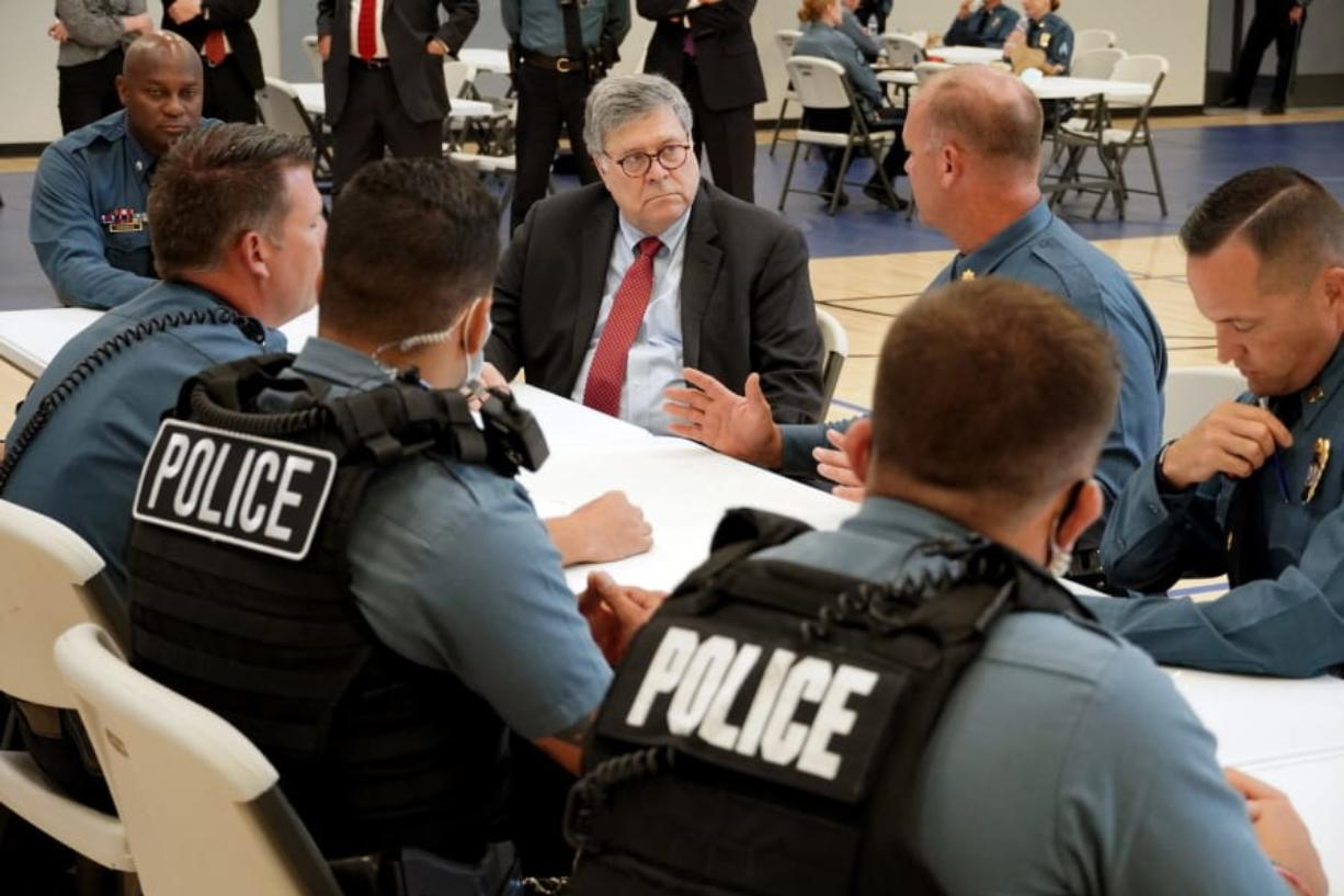 FILE - In this Aug. 19, 2020, photo Attorney General William Barr participates in a roll call with police officers from the Kansas City Police Department in Kansas City, Mo. In a private conference call this week with his U.S. attorneys nationwide, Attorney General William Barr said he wanted prosecutors to be aggressive in charging demonstrators who cause violence.