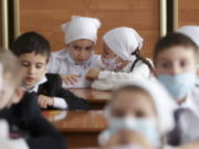 """Pupils wearing face masks to protect against coronavirus sit in a classroom during a ceremony marking the start of classes at a school as part of the traditional opening of the school year known as """"Day of Knowledge"""" in Grozny, Russia, Tuesday, Sept. 1, 2020. Across the country, schools start their usually festive opening day on Sept. 1."""